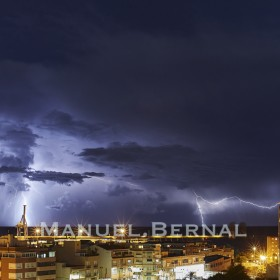 Photograph of a stormy night in Alicante with numerous lightning and lots of rain. Space for text.